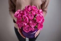 Reiches Bündel rosa Eustoma und Rosen blüht, grüner frischer Frühlingsblumenstrauß des Blattes in der Hand Blaues Meer, Himmel u  Lizenzfreies Stockbild