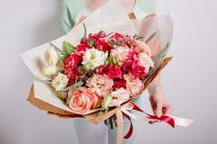 Reiches Bündel rosa Eustoma und Rosen blüht, grüner frischer Frühlingsblumenstrauß des Blattes in der Hand Blaues Meer, Himmel u lizenzfreie stockbilder