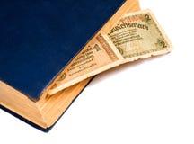 Reichsmarksräkning av Tyskland och den gamla boken som isoleras på vit Royaltyfria Bilder