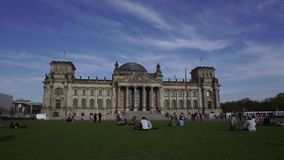 Reichstag Building, Berlin, Germany. April 15 2018: People relaxing on grass field in front of Reichstag Building above against sky, outdoors view, 4K filmed stock video footage