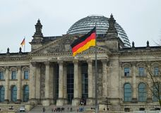 Reichstag building and German Unity Flag. Berlin, Germany - April 14, 2018: Fronton with pillars of Reichstag building with German Unity Flag on the foreground Royalty Free Stock Photography
