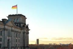 Reichstag byggnad med den tyska flaggan i solnedgång royaltyfri bild