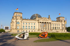 Reichstag taxi bike. BERLIN, GERMANY - MAY 22: Taxi bikes in front of the Reichtsag building on May 22, 2014 in Berlin, Germany. 5,334 kilometres of roads run Stock Image