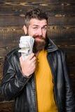 Reichtum und Wohl Hippie-Abnutzungslederjacke des Mannes grobe bärtige und Bargeld halten Mafiageschäft ungültig lizenzfreie stockbilder