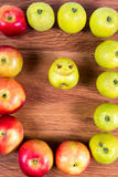 Reife Äpfel auf einem Weg breiteten einen Rahmen und einen Apfel mit einem Lächeln auf einem hölzernen Hintergrund aus Stockfotos