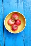 Reife Äpfel in der gelben Schüssel auf dem blauen Holztisch Lizenzfreies Stockbild