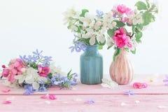 Reife Äpfel und Niederlassungen im Vase auf Weiß Stockfoto