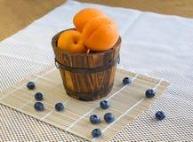 Reife Aprikosen in einem Eimer und in den Blaubeeren auf Weiß Stockfotografie
