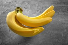 Reife Bananen auf grauem Hintergrund Stockfotografie