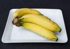 Reife Bananen auf weißer Platte Stockbild