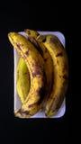 Reife Bananen in einer weißen Platte auf einem schwarzen Hintergrund Stockbilder