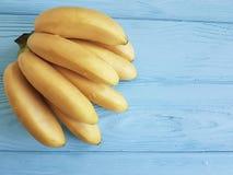 Reife Bananen exotisch auf einem blauen hölzernen Hintergrund lizenzfreies stockfoto