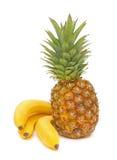 Reife Bananen und Ananas auf einem weißen Hintergrund Lizenzfreie Stockbilder