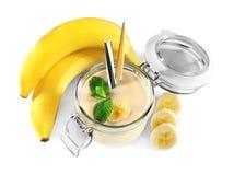 Reife Bananen und Glasgefäß mit geschmackvollem Smoothie Stockbilder