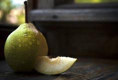 Reife Birne auf einem Holztisch mit Wasser fällt Lizenzfreie Stockfotos