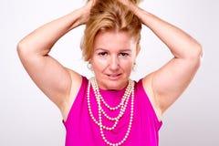 Reife blonde Dame mit beiden Armen oben Stockfotos