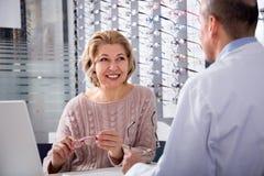 Reife blonde Frau berät sich mit professioneller männlicher Optik auf der Auswahl von Schauspielen Lizenzfreies Stockfoto