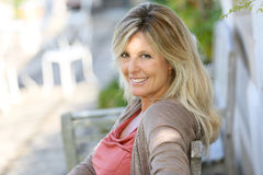 Reife blonde Frau, die auf Bank sitzt Lizenzfreies Stockfoto