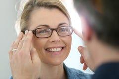 Reife blonde Frau, die auf Brillen versucht Lizenzfreie Stockfotos