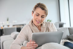 Reife blonde Frau, die auf Tablette websurfing ist Stockfotos