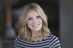 Reife blonde Frau, die an der Kamera lächelt Lizenzfreies Stockfoto