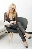 Reife blonde Frau, die ein Buch liest Lizenzfreie Stockbilder