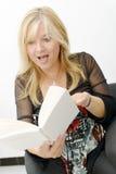 Reife blonde Frau, die ein Buch liest Stockbild