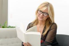 Reife blonde Frau, die ein Buch liest Lizenzfreie Stockfotografie