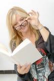 Reife blonde Frau, die ein Buch liest Stockfotos