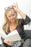 Reife blonde Frau, die ein Buch liest Lizenzfreies Stockbild