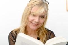 Reife blonde Frau, die ein Buch liest Stockfotografie