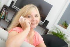 Reife blonde Frau, die am Handy spricht Lizenzfreie Stockbilder