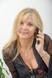 Reife blonde Frau, die am Handy spricht Stockbilder