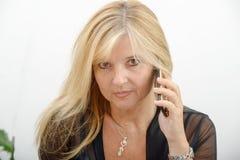 Reife blonde Frau, die am Handy spricht Lizenzfreie Stockfotos