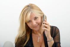 Reife blonde Frau, die am Handy spricht Stockfotografie