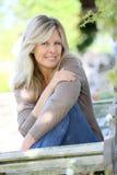 Reife blonde Frau, die im Garten aufwirft Stockbilder