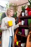 Reife blonde Frau, die keramischen Topf vorwählt stockfotos