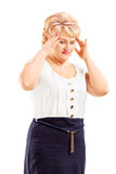 Reife blonde Frau, die Kopfschmerzen hat Lizenzfreies Stockbild