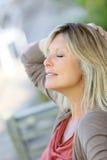 Reife blonde Frau, die sich draußen entspannt Lizenzfreie Stockbilder