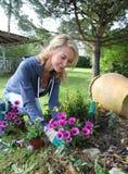 Reife blonde Frau, die zu Hause im Garten arbeitet Stockfotografie