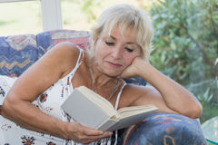Reife blonde Frau ist Lesebuch auf der Couch Stockbild