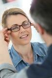 Reife blonde Frau mit im optischen Speicher, der auf Brillen versucht Stockfoto