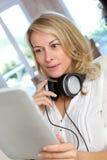 Reife blonde Frau mit Kopfhörern und Tablette Lizenzfreies Stockbild