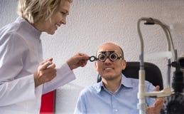 reife blonde Frau und ein Augenarzt des Mannes im Ruhestand überprüfen Sehvermögen in der Klinik Lizenzfreies Stockfoto