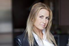 Reife blonde Frau, welche die Kamera betrachtet Stockfotos