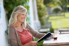 Reife blonde Frauenlesung und trinkender Kaffee Lizenzfreies Stockbild