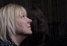 Reife Blondine, die zuhause aus einem Fenster heraus schauen Lizenzfreie Stockfotografie