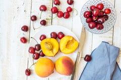 Reife bunte Pfirsiche halbiert und ganz, süße Kirschen auf weißer Platte, Kristallschüssel, Messer, hölzerne Tabelle der Planke,  Lizenzfreies Stockbild