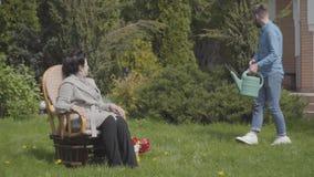 Reife Dame des Porträts, die auf dem Rasen im Schaukelstuhl genießt Sonne sitzt Erwachsener Enkel, der mit der Gießkanne kommt stock footage