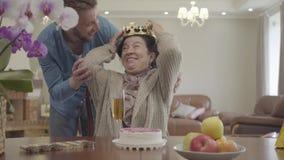 Reife Dame, die am Tisch vor kleinem Kuchen und an den Äpfeln auf der Platte sitzt Erwachsener Enkel holt die Krone und stock footage
